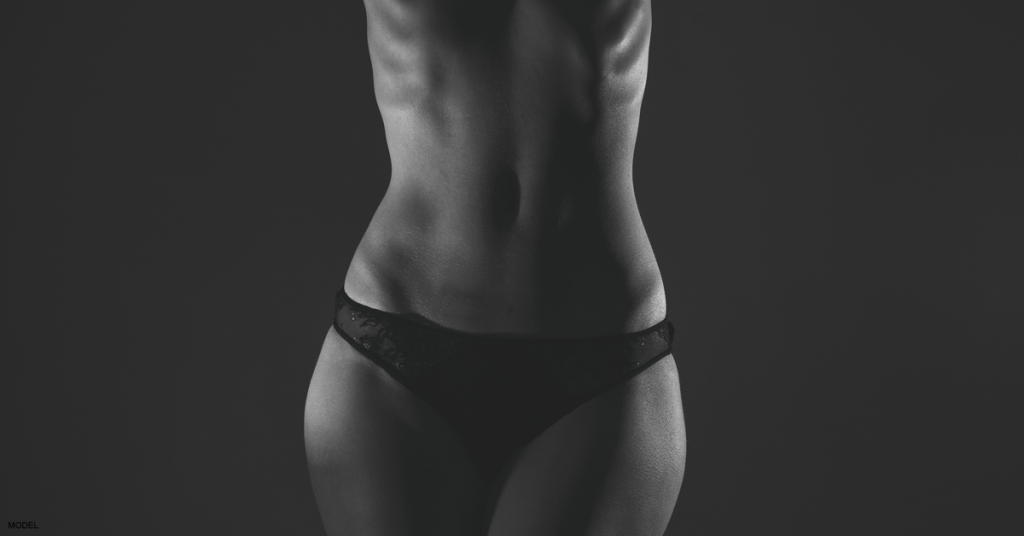Beautifully contoured woman's torso and upper thighs wearing black, lacy panties